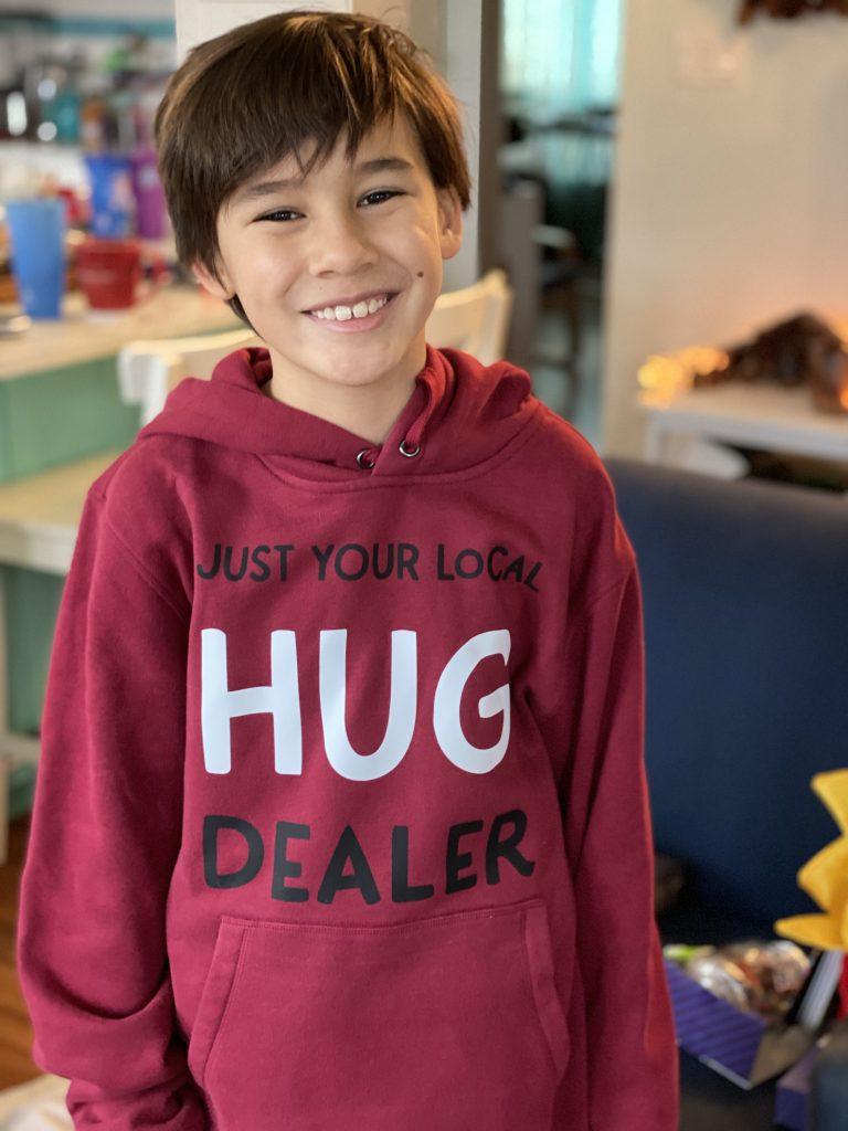 Adorable boy wearing a  DIY Just Your Local Hug Dealer hoodie.