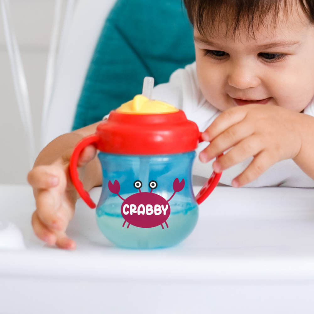 Baby holding a sippy cup with a crab that says crabby on its shell.