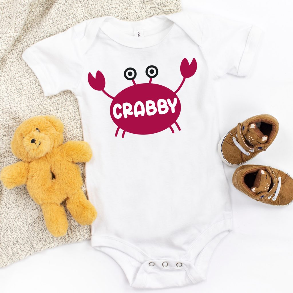 """White onesie with a hand drawn crab that says """"Crabby"""" on his shell."""